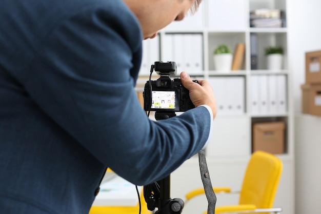 スーツの男性の腕が三脚にビデオカメラをマウント