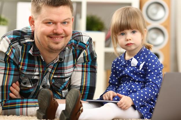 お父さんと床のカーペットにかわいい女の子