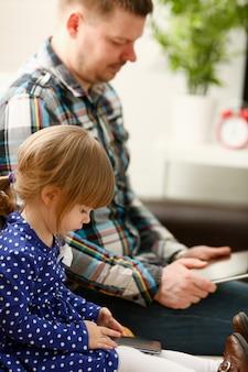 お父さんとソファの上のかわいい女の子は携帯電話を使用します