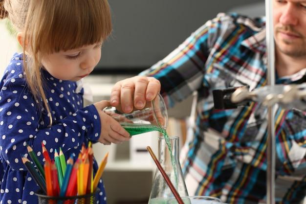 Мужчина и маленькая девочка играют с разноцветными жидкостями