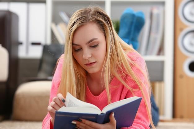 Молодая красивая белокурая женщина лежит на полу и читает книгу