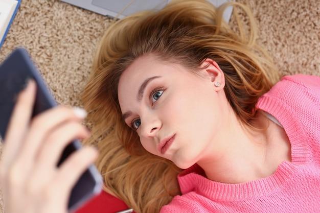 Молодая красивая женщина отдыхает, лежит на полу, держит смартфон в руках