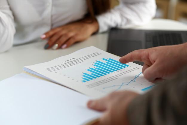 財務グラフと銀のペンを保持している女性の腕