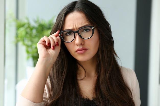 メガネを保持している若い美しいビジネス女性