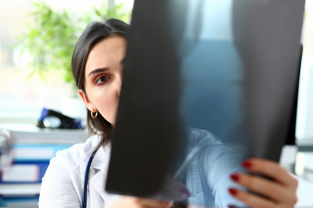 Женский красивый доктор держать в руке и посмотреть на рентген