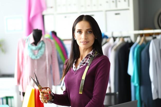 ファッションデザイナーの女性は彼女の手ではさみを保持しています。