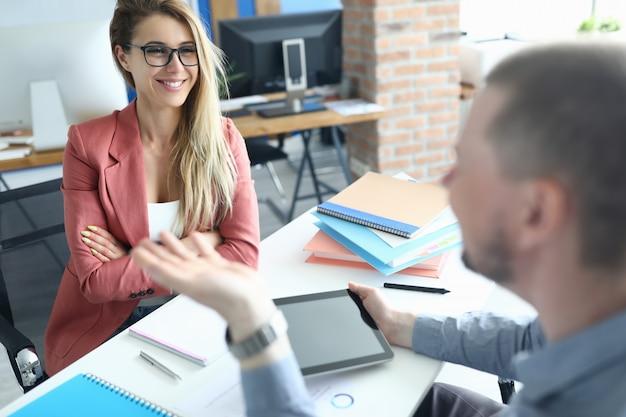 ビジネスマンおよび現代オフィスの背景の肖像画に対して話している女性