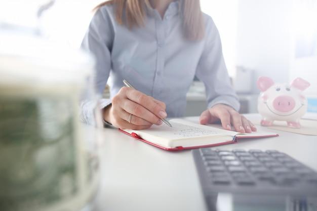 女性の手を保持する銀のペンはノートを作る