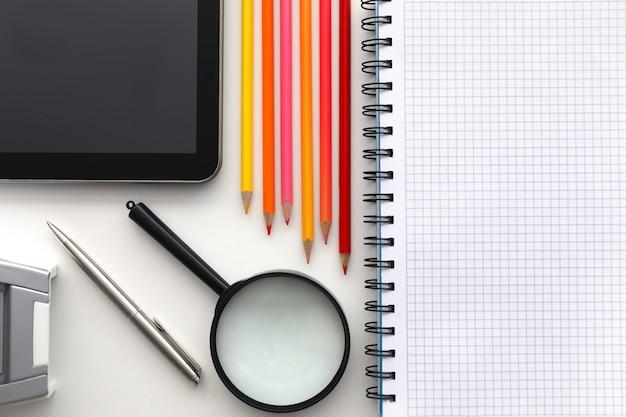 Планшетный пк и набор карандашей на фоне рабочего стола крупным планом