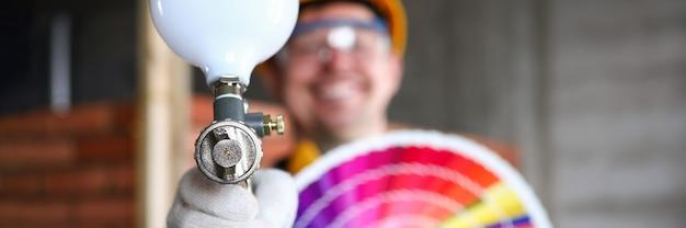 Улыбающийся строитель показывает краскопульт и образцы цветов