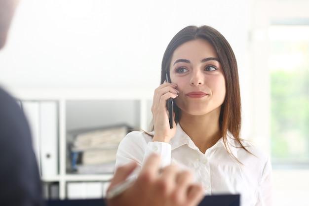 美しいブルネット笑顔実業家話携帯電話