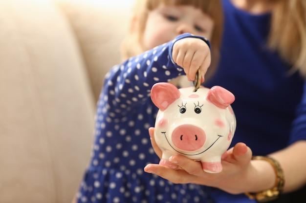 Рука маленькой девочки ребенка кладя монетки в копилку