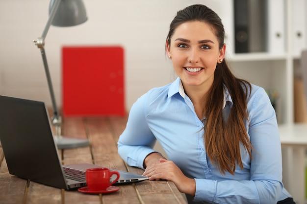 Портрет деловой женщины с ноутбуком. женщина смотрит в камеру и улыбается.
