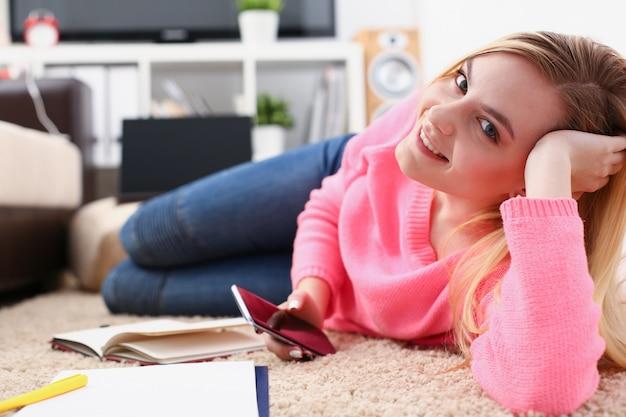 Молодая красивая блондинка на диване держать смартфон в руках