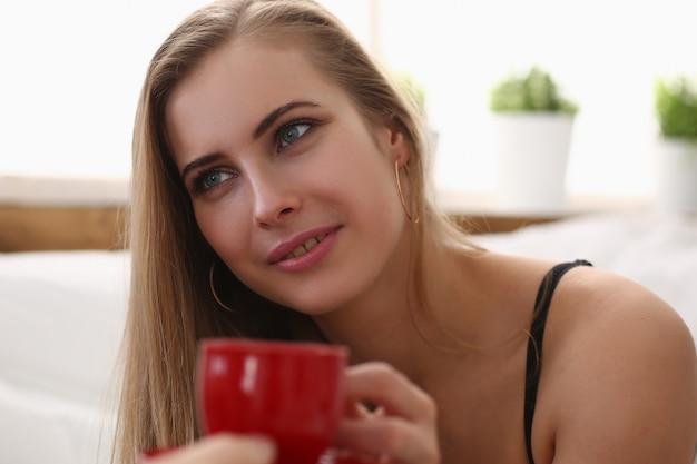 早朝のコーヒーのカップを持つ美しい女性