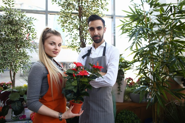 Радостный молодой мужчина и женщина, работающая в цветочном магазине
