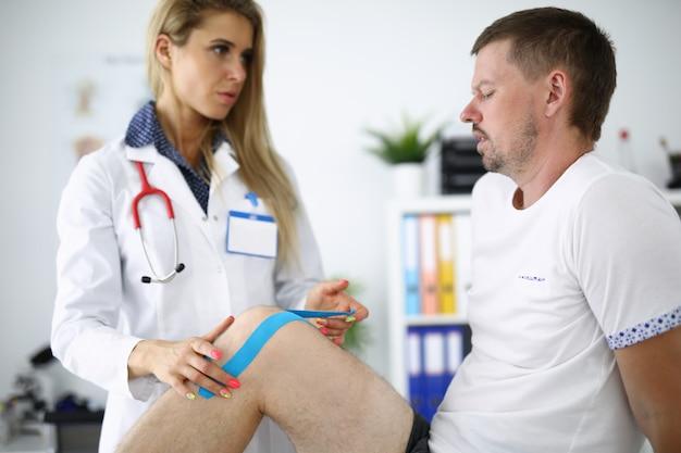 Женщина-врач фиксирует кинезио ленту на колене пациента.