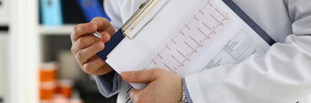 男性医師の手はクリップボードパッドで患者の履歴リストを埋める銀のペンを保持します。