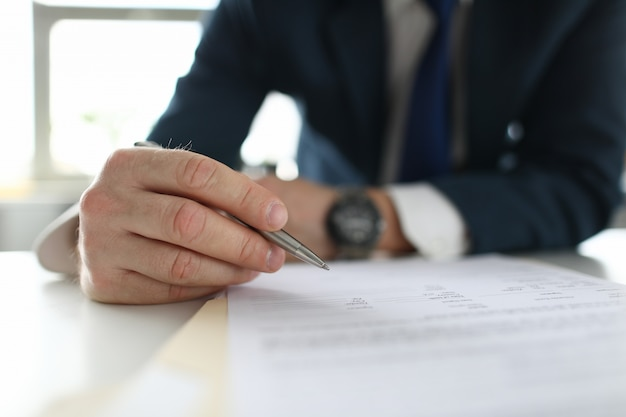 ビジネススーツを着た男の手がテーブルでメモをとります。プロのキャリアと自己利益で忙しいビジネスマン
