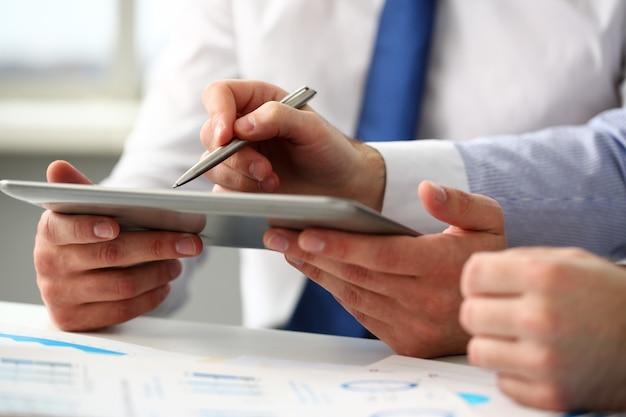 ビジネスマンのグループは腕の中で指と銀のペンを指す