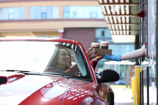 車の中で女性は彼女のコーヒーのコンセプトをピックアップ
