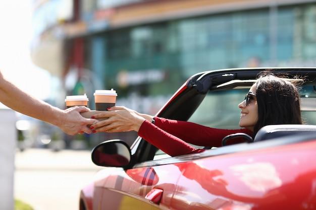 宅配便は車のクローズアップで女性にコーヒーを引き渡す