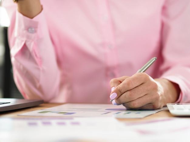 女性は職場に座って、グラフにメモを取ります