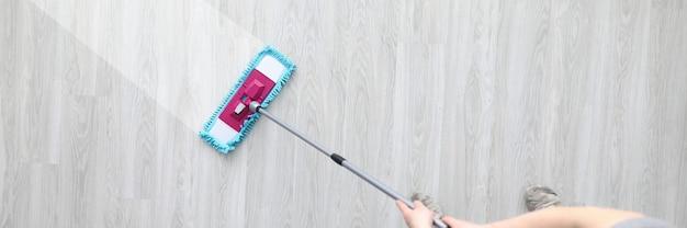 男性ハントプラスチックモップを保持し、汚れた床を洗う