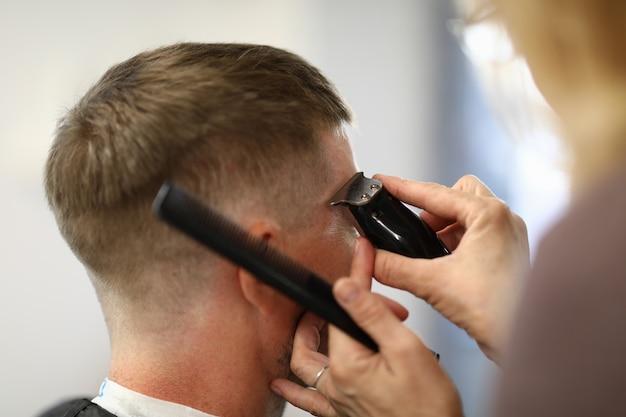 美容師は、美容院でバリカンで男をカットします。美容師職業訓練コンセプト