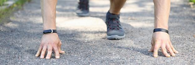 公園での実行の準備をしているプロのスポーツ選手のクローズアップ。快適なスタイリッシュなグレーのスニーカーを着た男性。