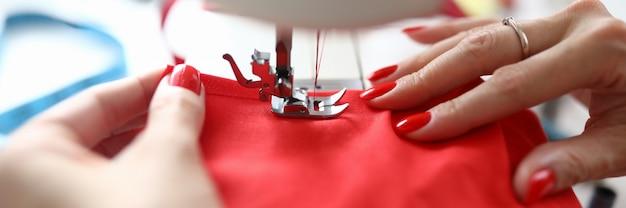 仕事にミシンを使ってプロの女性仕立て屋のクローズアップ。