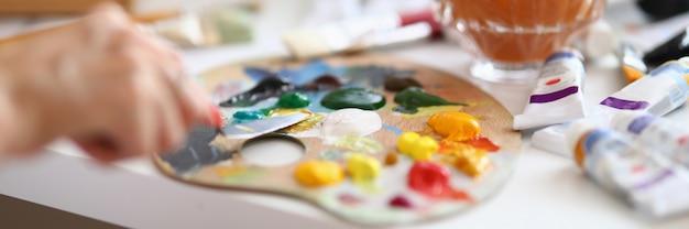 パレットに油絵の具を混ぜる画家のクローズアップ。
