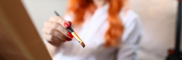 油絵の具で絵筆を保持している赤い髪の女性のクローズアップ。