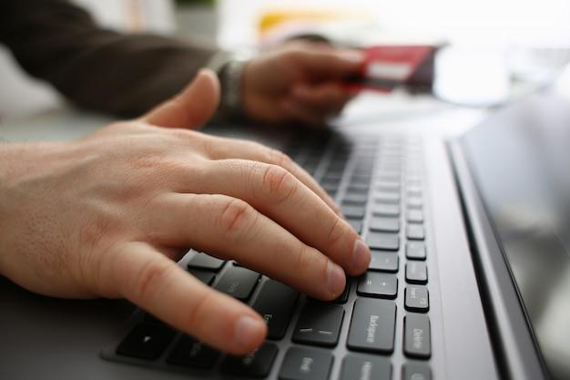 ノートパソコンに入力する銀行カードを持つ男