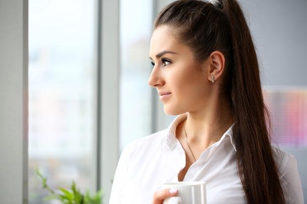 美しい笑顔の女の子を腕の中で保持する大きなカップの肖像画