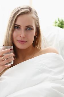ブロンドの女性はベッドで早朝の滞在で腕の中で水のガラスを保持します