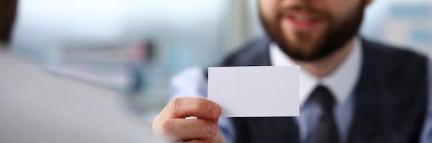 スーツの男性の腕は、訪問者に空白のコーリングカードを与える