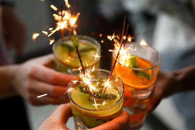 Молодые друзья группы держат в руке коктейль с бенгальским огнем