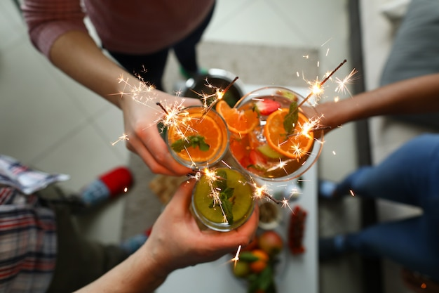 若いグループの友人が手で線香花火とカクテルを保持します。
