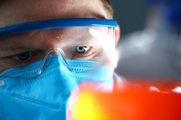 保護マスクを身に着けている実験室の男が手にテストサンプルを保持します。
