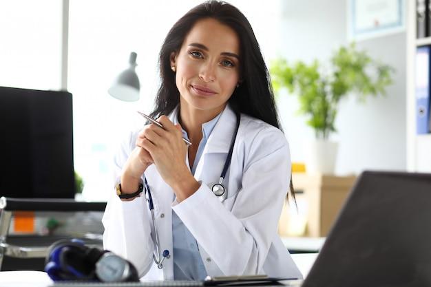 Женский врач сидит за рабочим столом в офисе