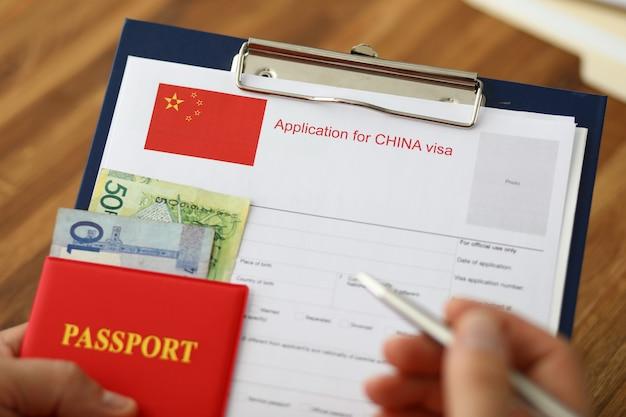 男性の手はパスポートと銀のペンを保持します