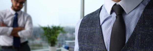 青いスーツの男性の腕セットネクタイのクローズアップ