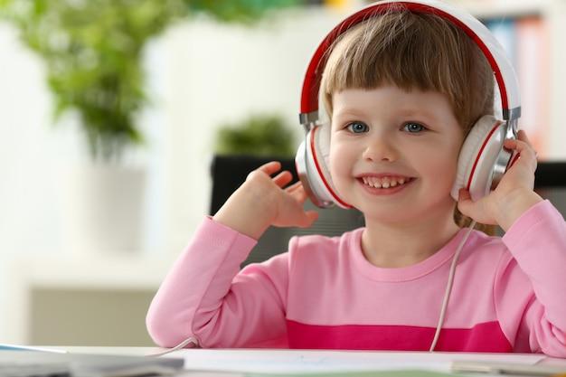 座っているヘッドフォンで満足している子