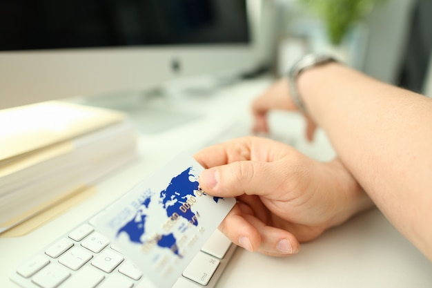 Мужская рука держит пластиковую банковскую карту аганиста
