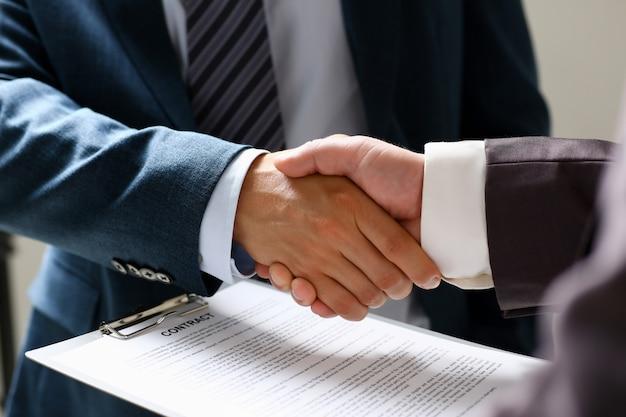 Мужчина в костюме пожимает руку как привет в офисе крупным планом