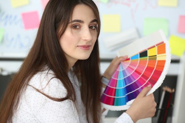 美容デザイナーの女性は手にカラーパレットを保持します。