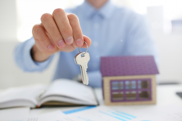 Мужская рука держит ключ от замка в руке на фоне