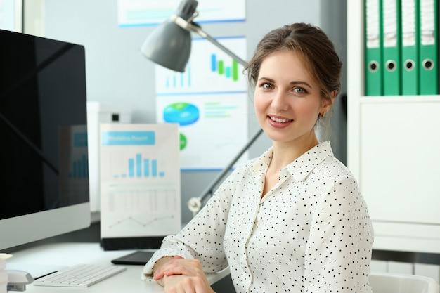 職場に座っている陽気な女性