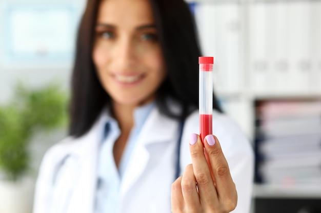 赤い液体を含むプラスチック試験管を持っている女性医師の手